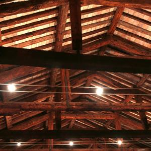 Image of the roof from the inside with a string of light bulbs hanging down across