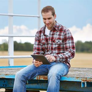 Image of a man sitting on a bench reading his tablet