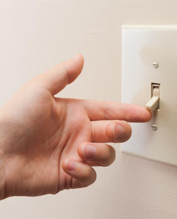 photo of a hand flicking on a light switch