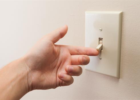 Image of a hand turning on a light switch
