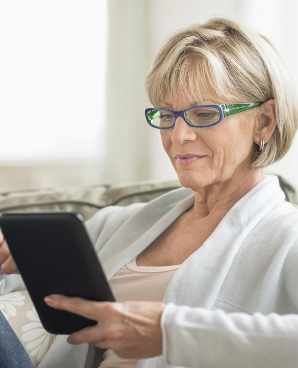 photo of a woman holding a tablet to sign up for outage alerts