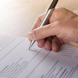 Image of a hand holding a pen filling out an insurance claims form