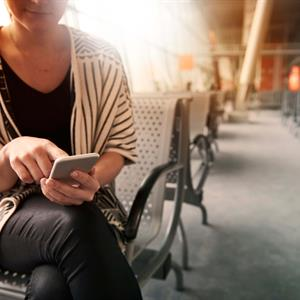 image of a woman using a mobile device to receive high usage alerts