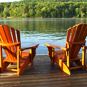 photo of two muskoka chairs on a dock