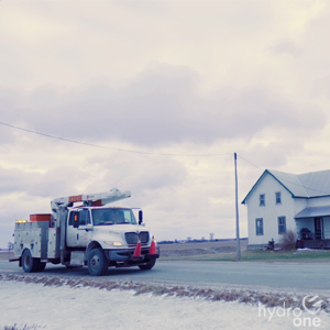 photo of a Hydro One truck in front of an old farmhouse