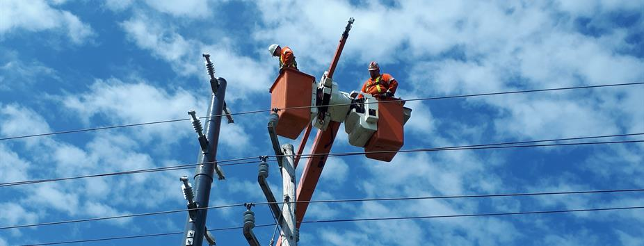 photo of Hydro One workers fixing a wooden distribution pole
