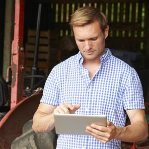 Image of a farmer holding a tablet computer