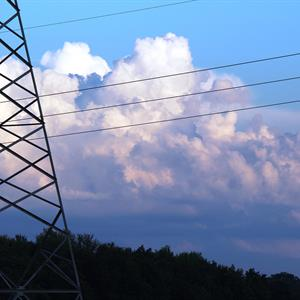 Image of a transmission tower with power lines against a cloud background