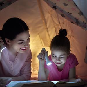 Image of a mother and daughter reading by flashlight