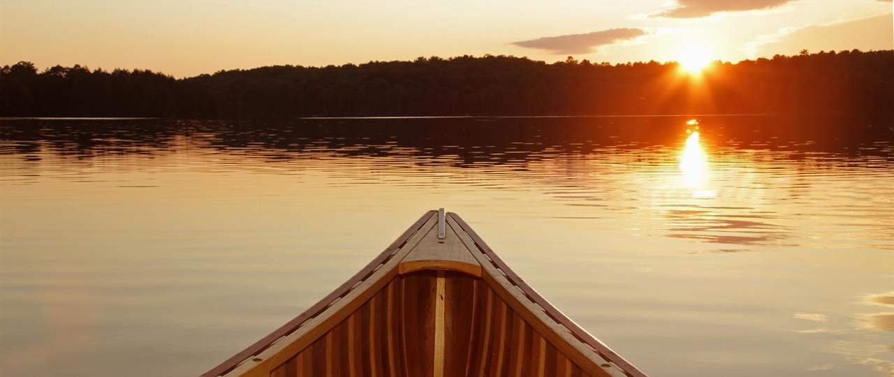 photo of a canoe on a lake at sunset