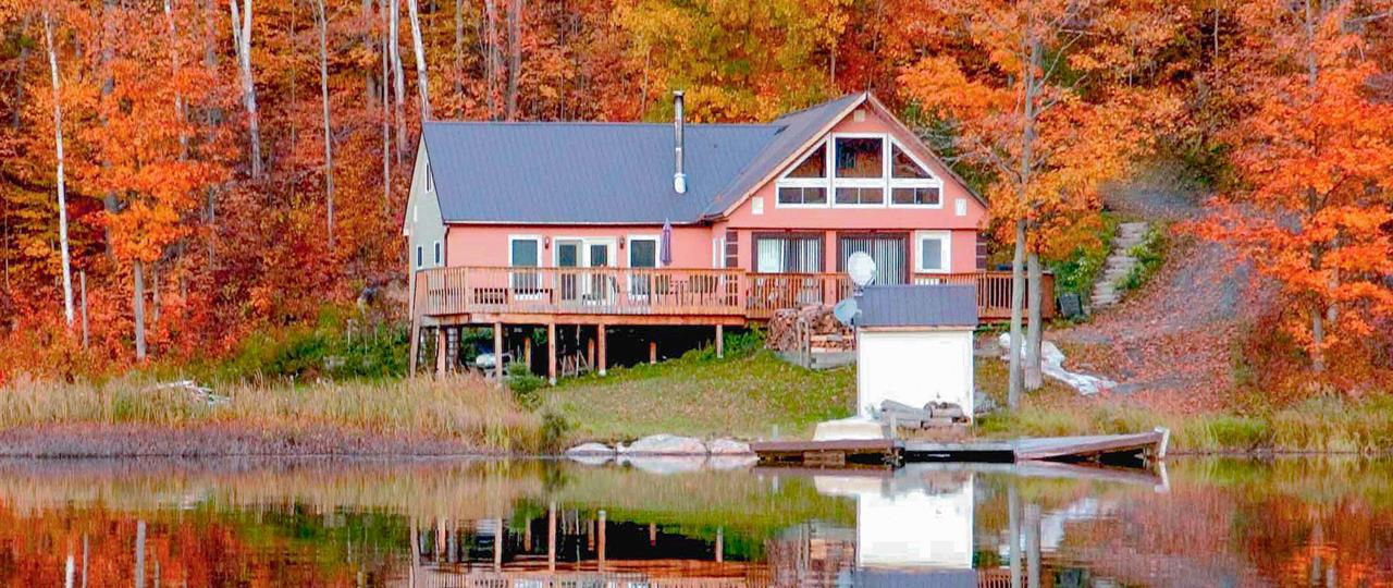 photo of a cottage on a lake in fall