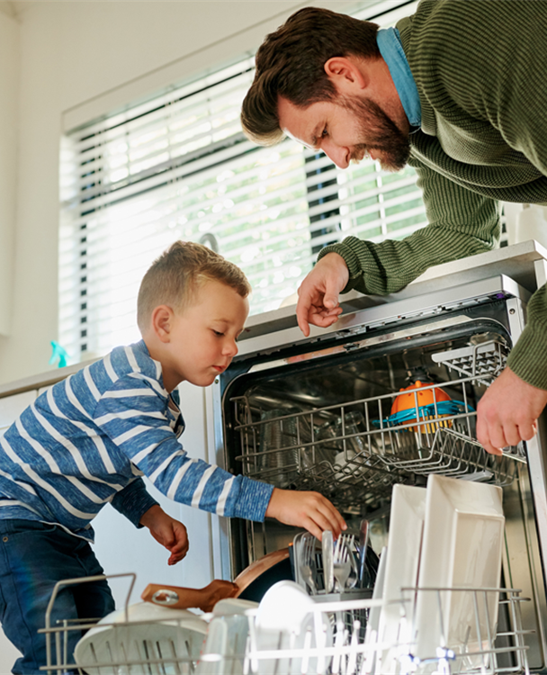 photo of a dad and his young son loading a dishwasher
