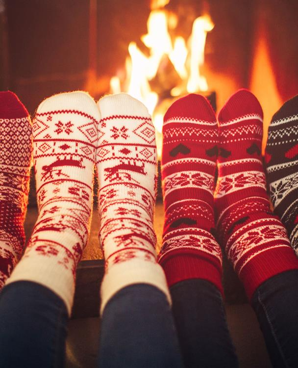 four sets of feet in holiday socks in front of a fire in a fireplace