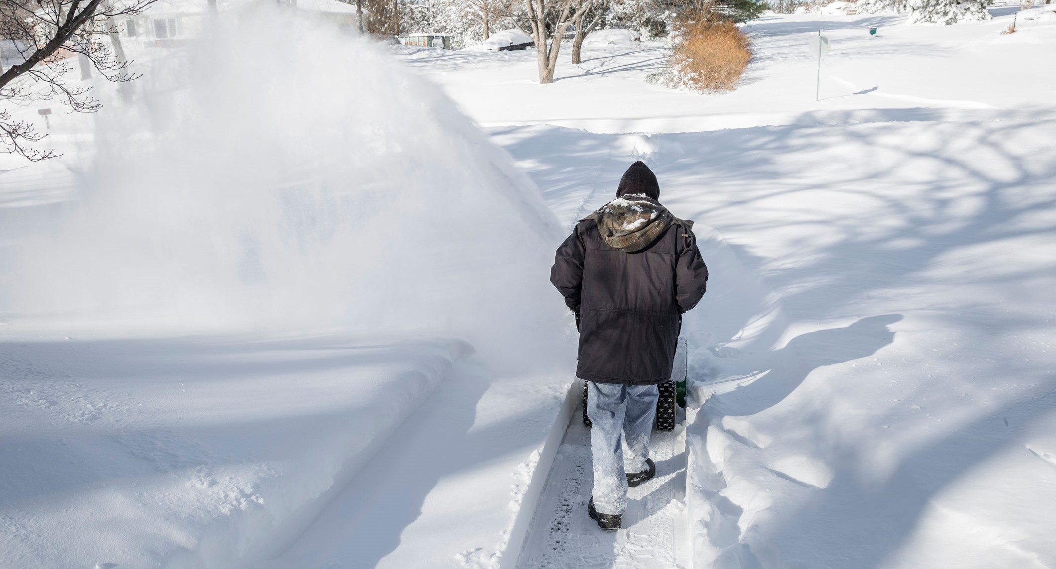 A man from behind pushing a snowblower in a driveway after a blizzard