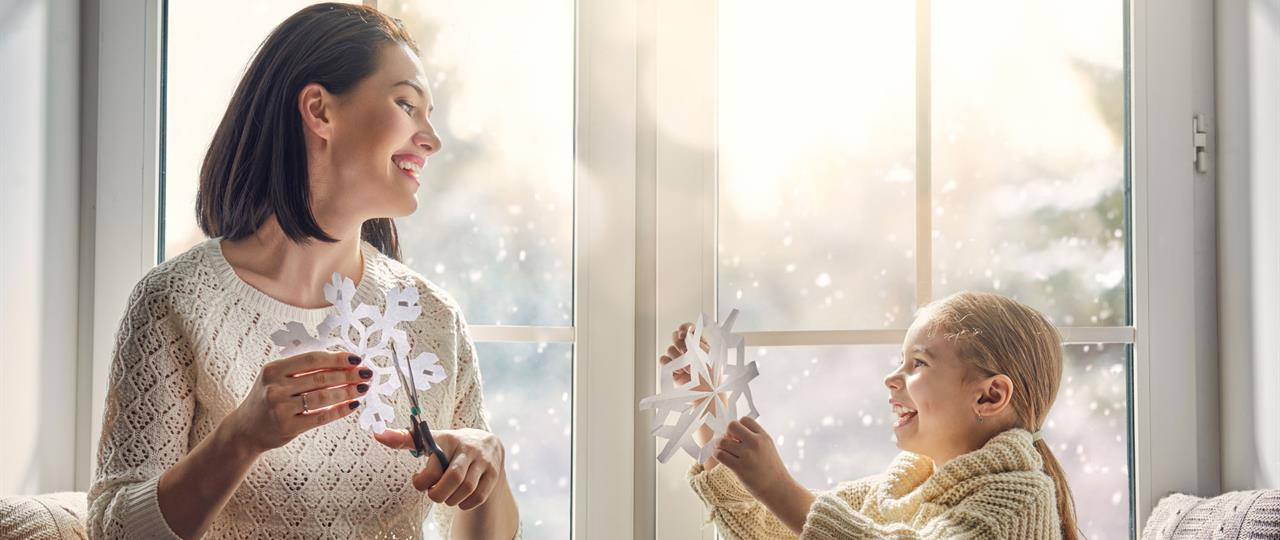 a mom and child cutting snowflakes in front of a window