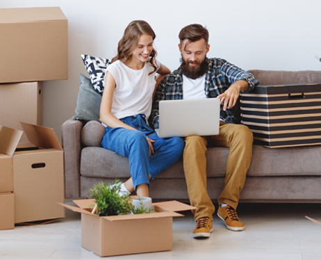 photo of a couple sitting on a couch using a laptop with moving boxes all around them