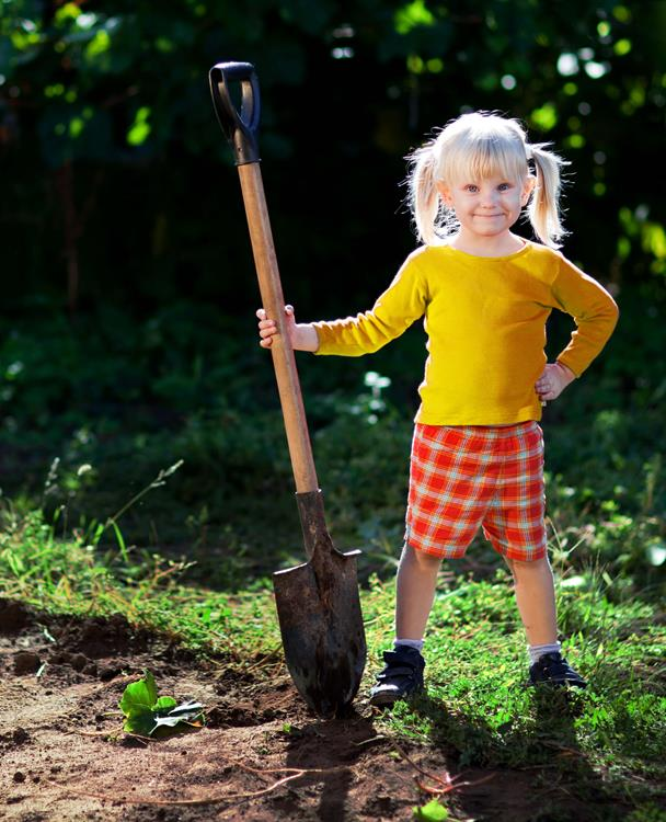 photo of a young girl standing in a garden holding a shovel