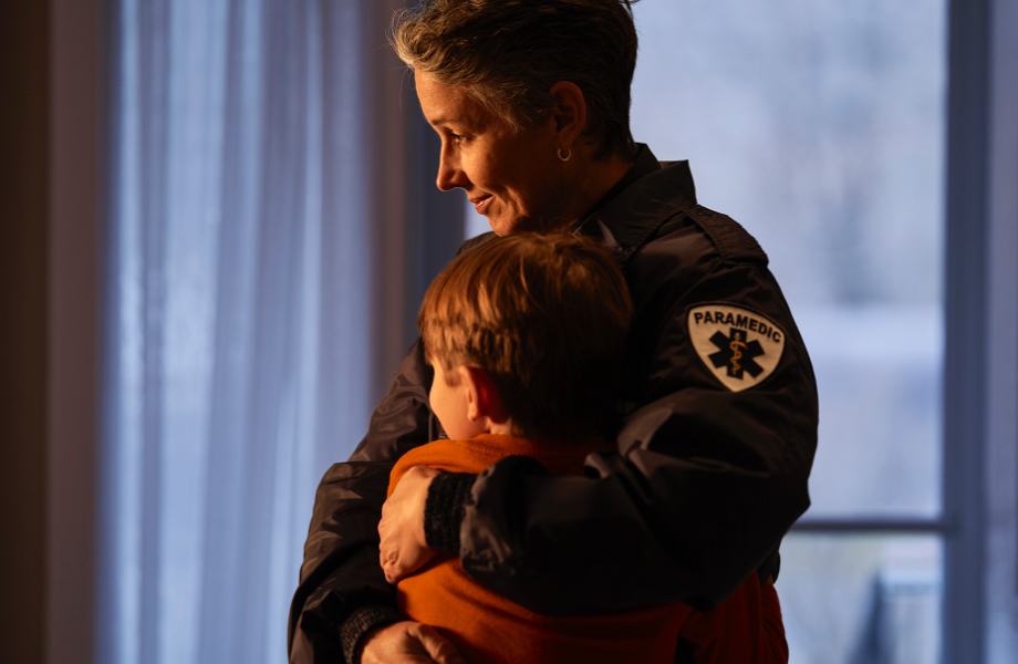 a paramedic in uniform hugging her son