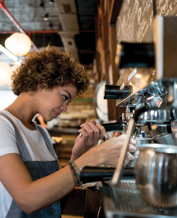 a female barista using an espresso machine