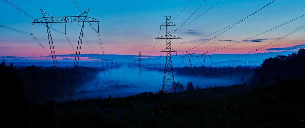 sunrise with a blue and pink skies overlooking a field with transmission lines