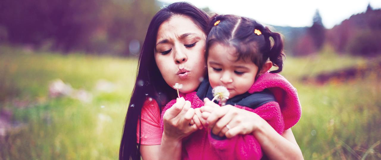 a mom and daughter blowing flowers in a field