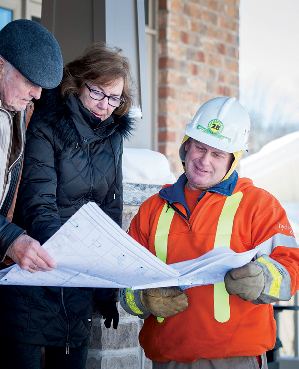 a customer lookng at blue prints outside in the snow with a Hydro One employee