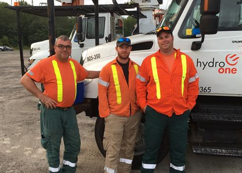 Forestry crew in front of a Hydro One truck who saved the life of an elderly woman hit by a car
