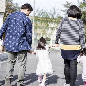 Image of a family holding hands while walking