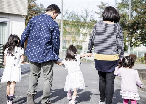 Image of a family holding hands and walking
