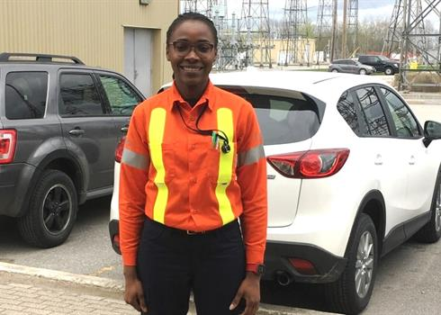 photo of Linda Chigbo standing in front of a Hydro One transformer station