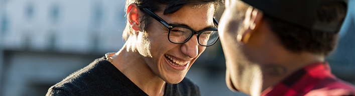a close up shot of a man with glasses smiling