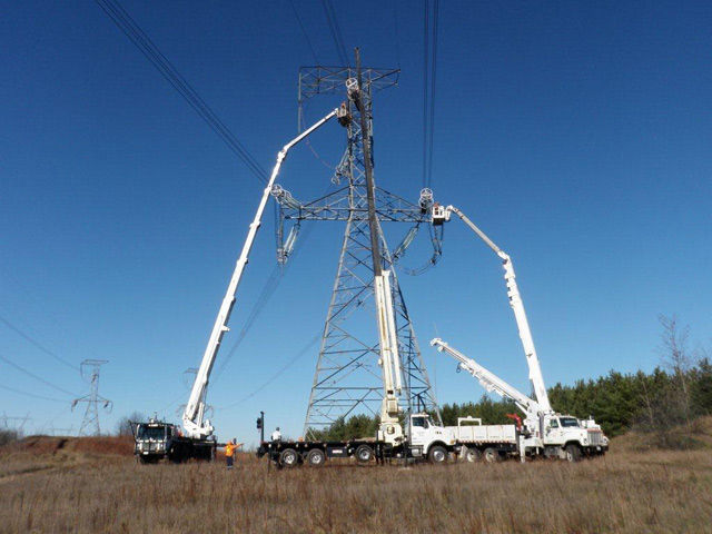 photo example of Hydro One vehicles working around a transmission tower which demonstrates why a 15-metre clear working radius is required