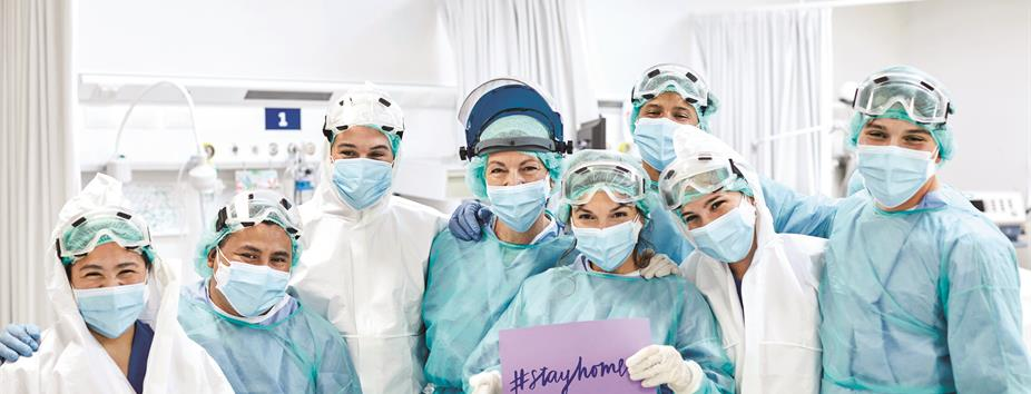 photo of nurses wearing scrubs holding a sign that says Stay Home