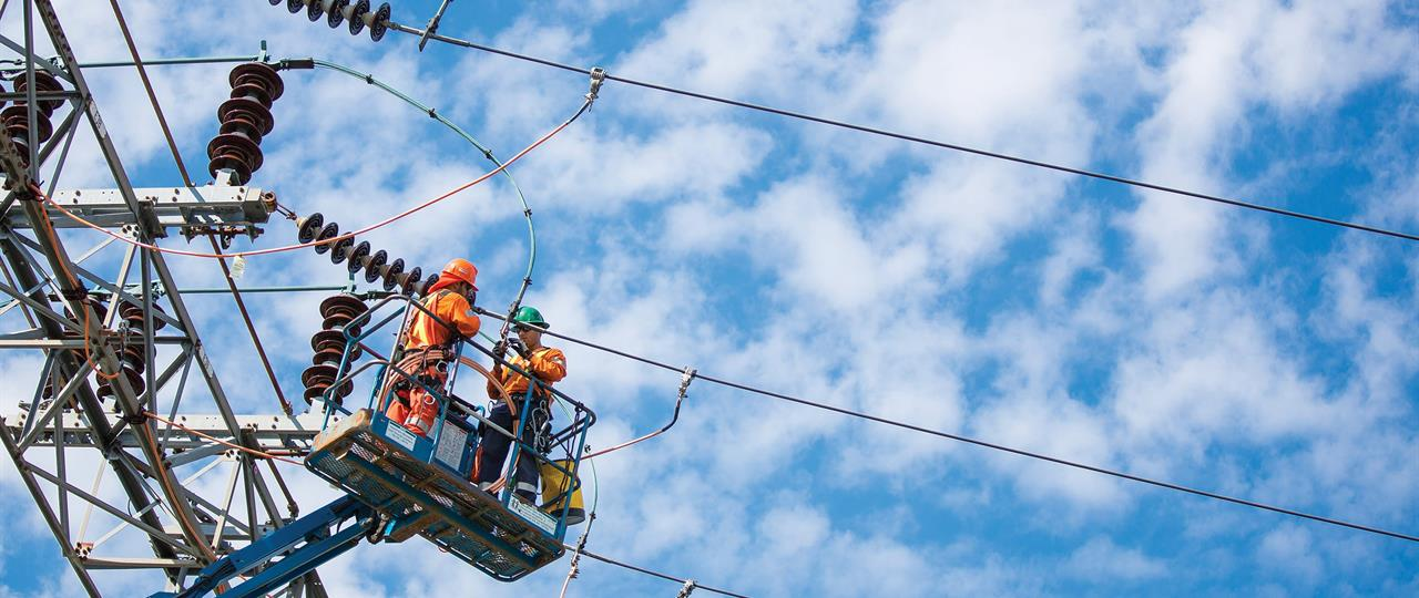 Photo of Hydro One linemen working on a transmission tower
