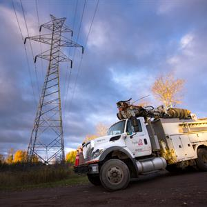 photo of a Hydro One vehicle in front of a transmission tower