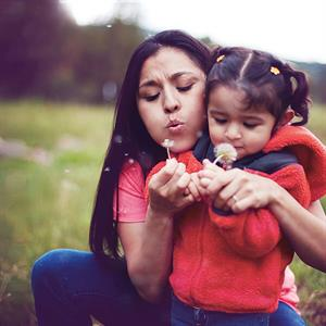Image of a woman and daughter blowing on a flower