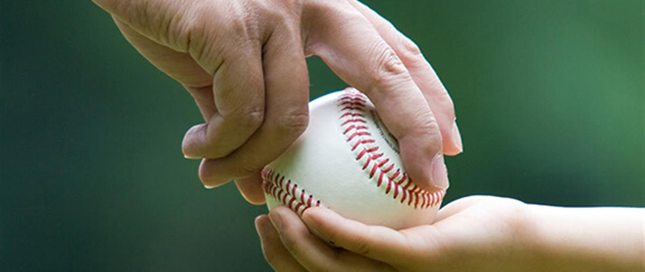 photo of an adult hand putting a baseball in a child's hand