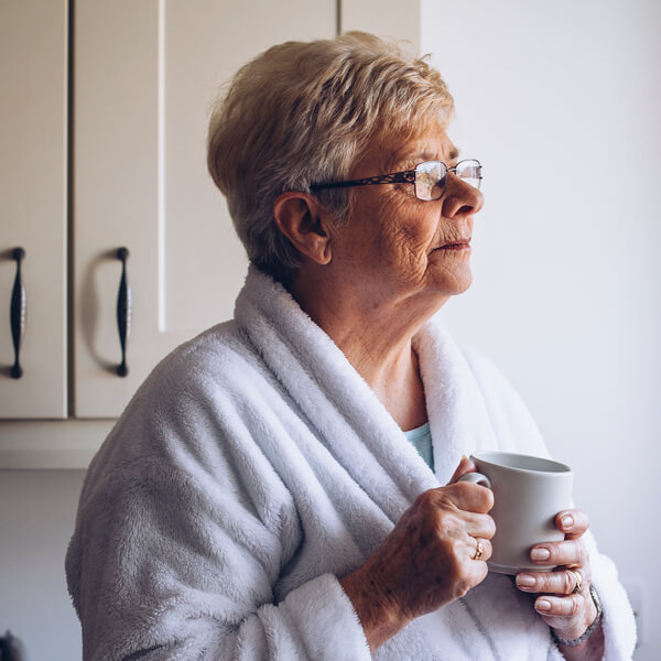 Senior woman holding a mug, looking out a sunny window