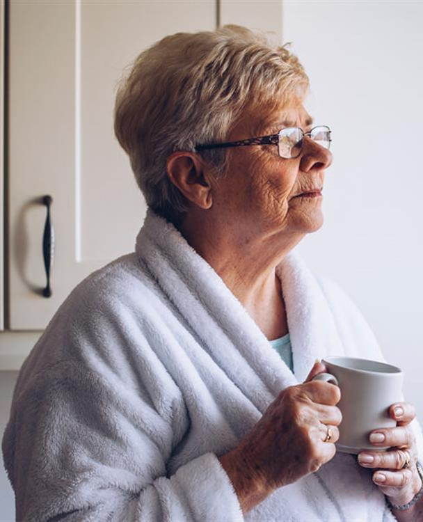 photo of an older woman in a housecoat holding a coffee mug